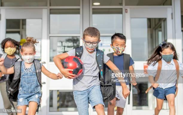 diversi gruppi di bambini delle scuole elementari tornano a scuola indossando maschere - bambino di scuola elementare foto e immagini stock