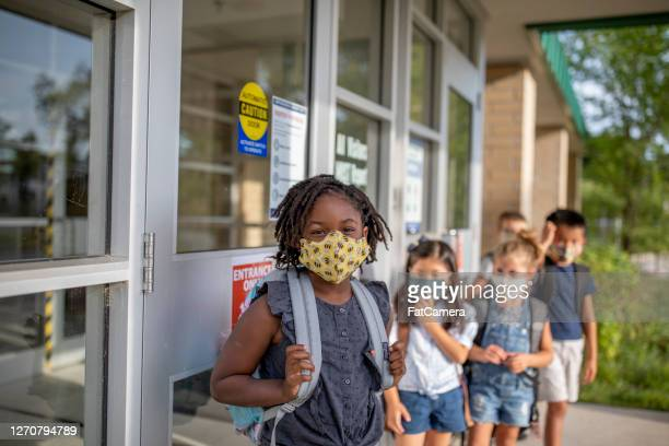 diverse group of elementary school kids go back to school wearing masks - fatcamera stock pictures, royalty-free photos & images