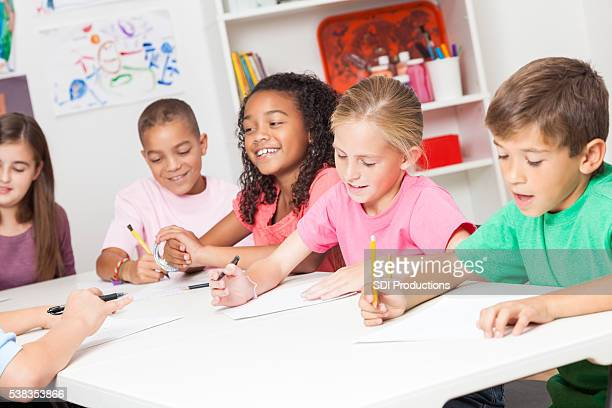 Diverse group of elementary school kids work in class