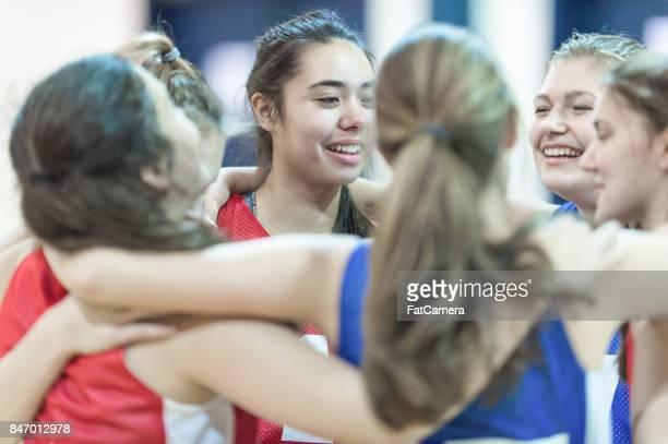 Heterogene Gruppe von weiblichen Basketball-Spieler nach dem Spiel umarmen