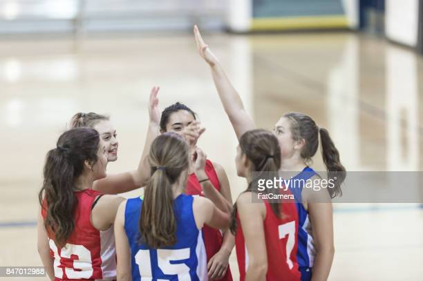 diverse group of female basketball players in a huddle giving high five's - basketball team stock pictures, royalty-free photos & images