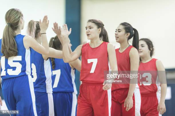 Diverse group of female basketball teams giving high five's