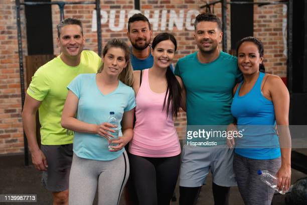 Diverse group of fit people at the gym smiling at camera