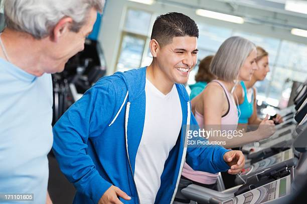 Diverse group of fit people running on treadmills in gym