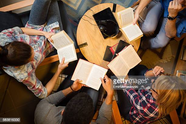 Diverse group of friends discussing a book in library.