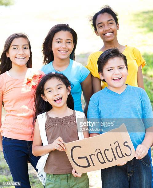 diverse group of friends hold 'gracias' sign - thank you phrase stock pictures, royalty-free photos & images