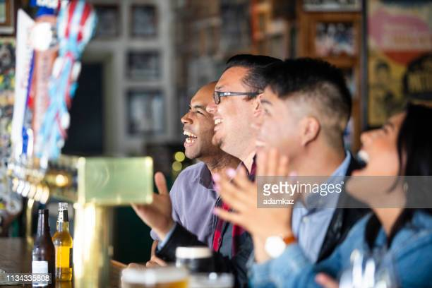 diverse group of friends watching game at sports bar - home run stock pictures, royalty-free photos & images