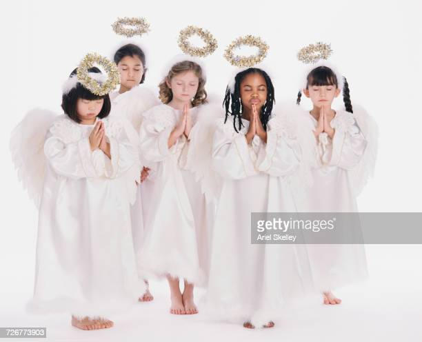 Diverse group of girls wearing angel costumes praying