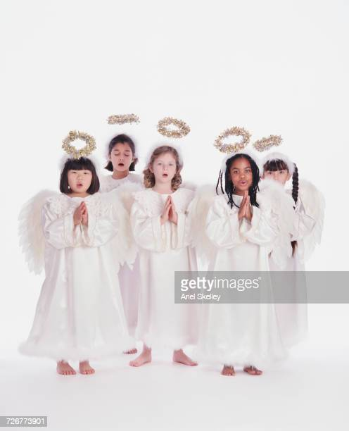 Diverse group of girls wearing angel costumes singing and praying