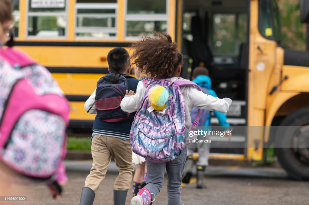 Diverse group of happy children getting on school bus : Stock Photo