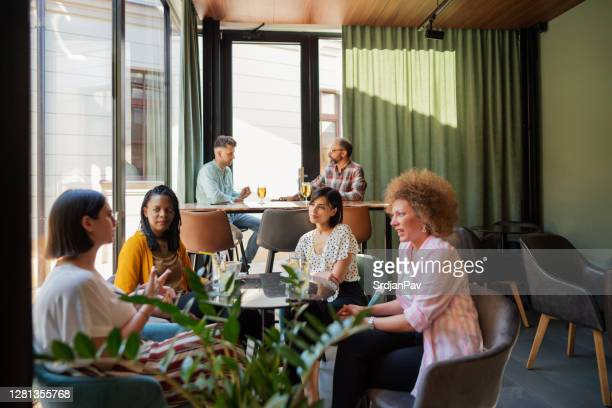 diverse group of ladies wearing casual clothes talking at the coffee shop - good; times bad times stock pictures, royalty-free photos & images