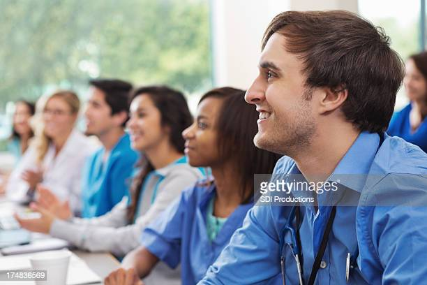 Diverse group of medical sudents listening intently in college classroom