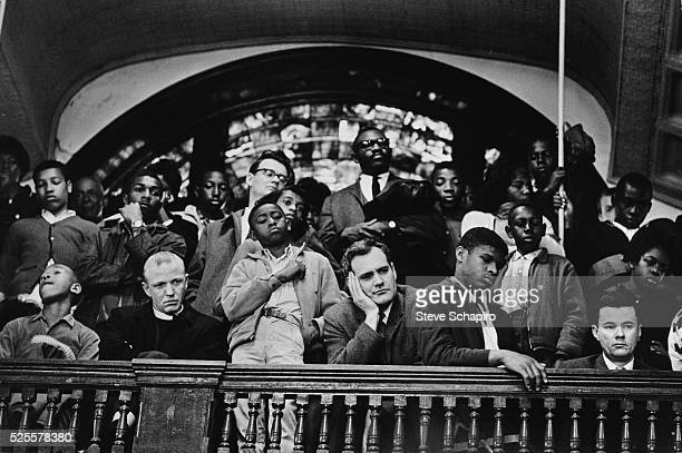 A diverse group of parishioners listen to Dr Martin Luther King Jr speak from a in a church balcony in Selma Alabama
