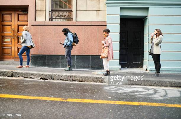 diverse group of people in face masks social distancing on a city sidewalk - south africa stock pictures, royalty-free photos & images