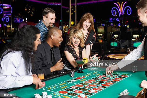 Diverse Group of People Playing Roulette In a Casino