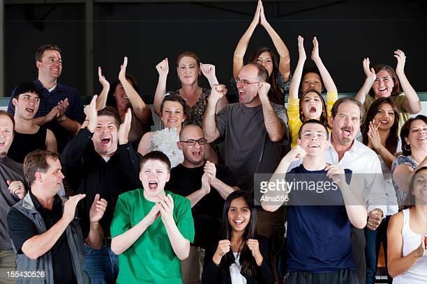Groupe diversifié de gens debout et acclamations au jeu
