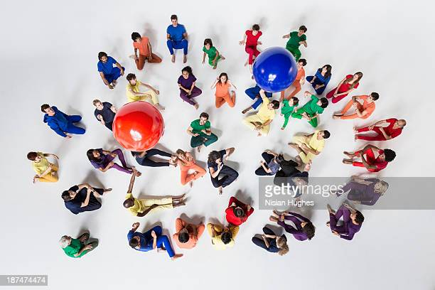Diverse Group of People Tossing Blue and Red Balls