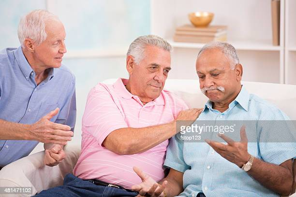 Diverse group of senior men console a friend. Home setting.