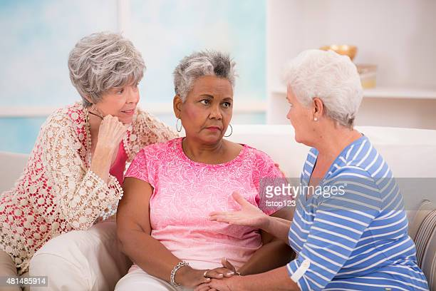 Diverse group of senior women console a friend. Home setting.