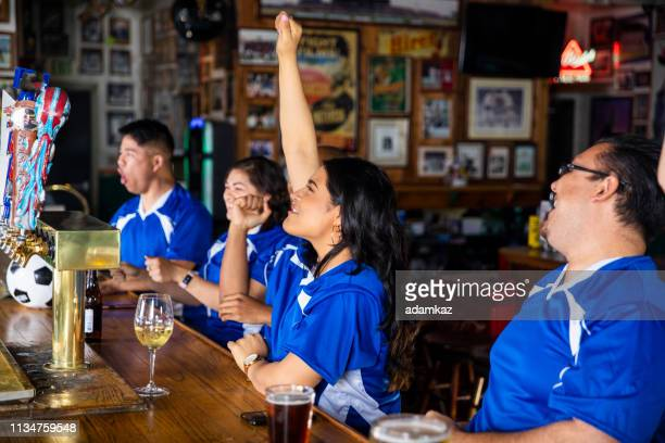 diverse group of sports fans cheering at the bar - home run stock pictures, royalty-free photos & images