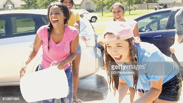 diverse group of teenage girls playing at a car wash - fundraising stock pictures, royalty-free photos & images
