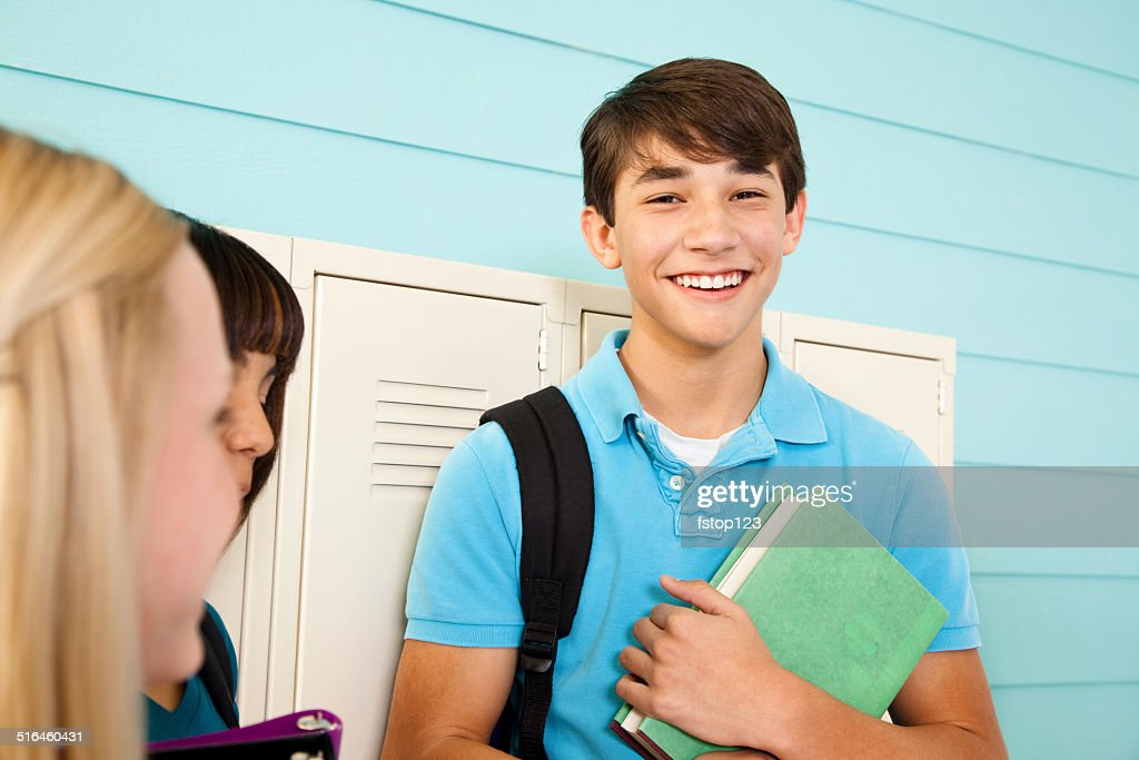 Diverse group of teenage students talk in school hallway. Lockers. : Stock Photo