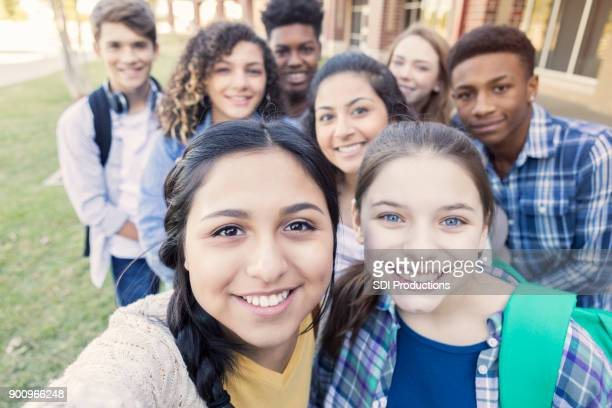 diverse group of teens looking at camera taking selfie at high school - teenagers only stock pictures, royalty-free photos & images