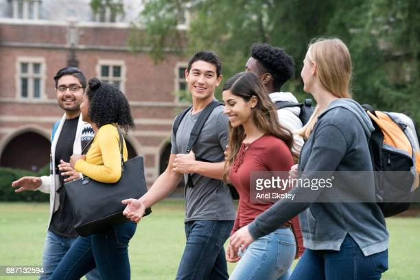 diverse group of university students walking on campus - college student stock pictures, royalty-free photos & images