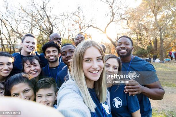 diverse group of volunteers crowds together for selfie - selfless stock pictures, royalty-free photos & images