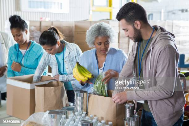diverse group of volunteers in food bank - food bank stock pictures, royalty-free photos & images