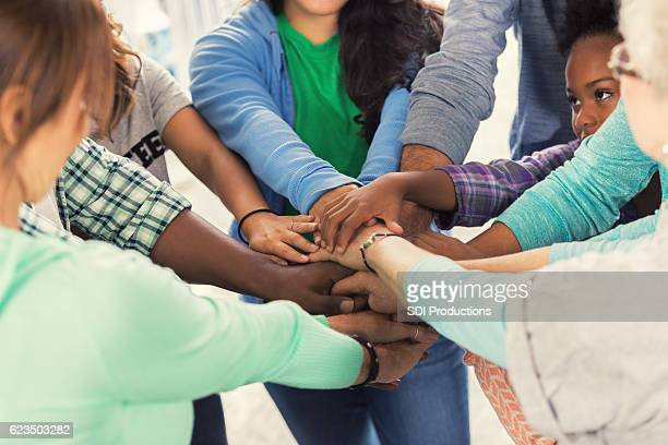 diverse group of volunteers put hands together - humanitarian aid stock pictures, royalty-free photos & images