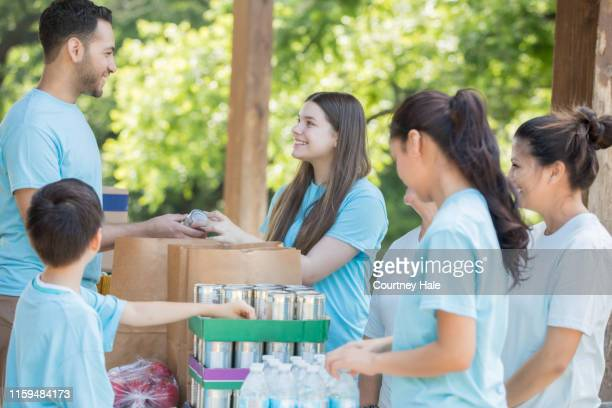 diverse group of volunteers sort donated canned food during community outreach event - food drive stock pictures, royalty-free photos & images