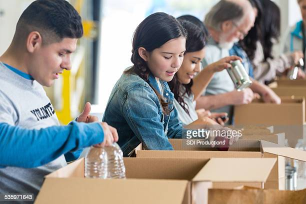 diverse group of volunteers sorting food donations into boxes - humanitarian aid stock pictures, royalty-free photos & images