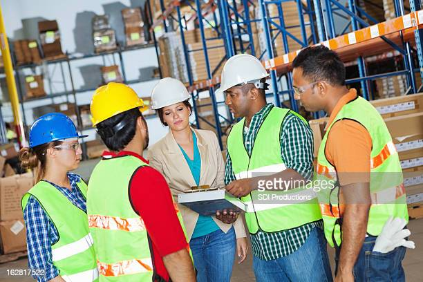 Groupe diversifié de travailleurs examinant entrepôt travail avec le directeur