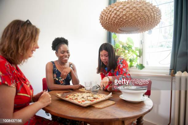 Diverse group of women cutting their freshly baked pizza