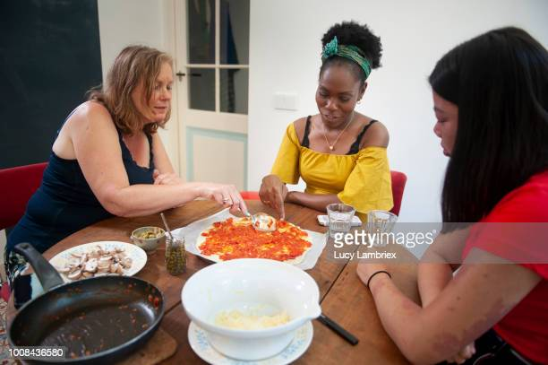 Diverse group of women preparing ingredients for a pizza