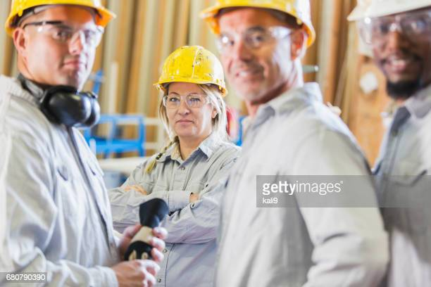 Diverse group of workers in hardhats, focus on woman