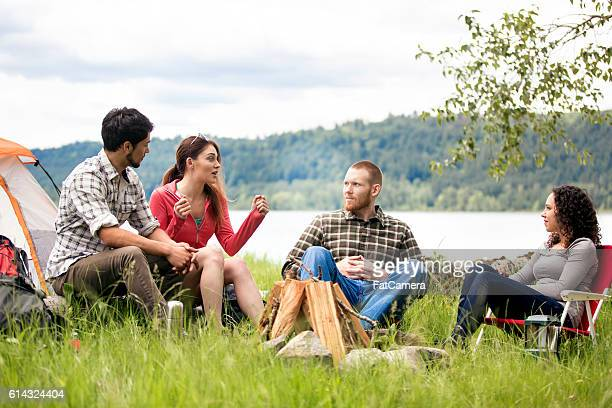 Diverse group of young adults sharing stories around a campfire