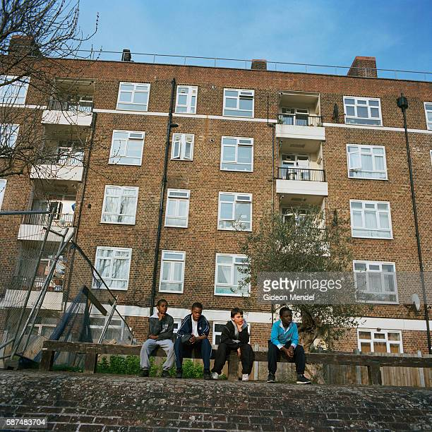 A diverse group of young boys whose parents come from Africa and Kosovo watch their friends playing on the Kingsmead Estate in Homerton in the...