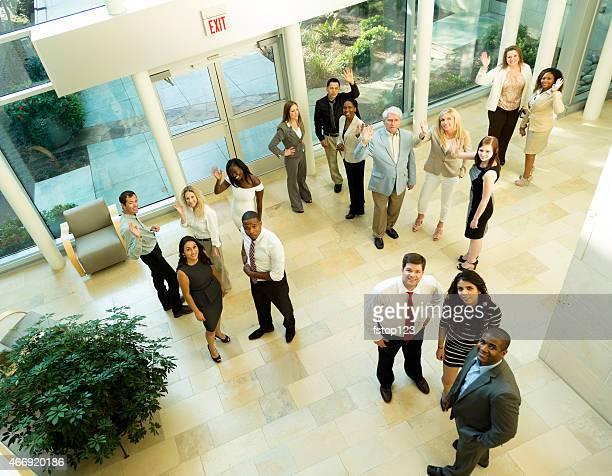 多様なグループオフィスで働くビジネス人々は、ロビーのエントランスに入ります。ハイアングル。