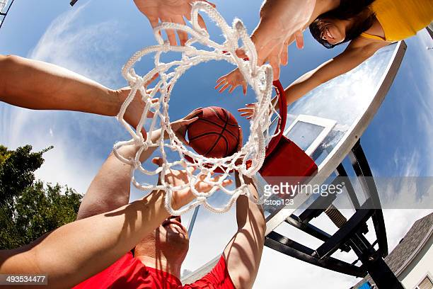 Diverse group, young adults playing basketball. Low angle view. Goal.