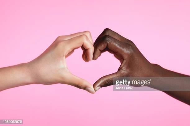 vielfältige hände mit liebeszeichen - ethnische zugehörigkeit stock-fotos und bilder