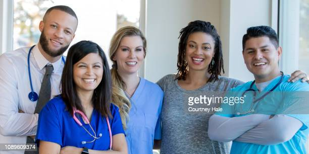 diverse healthcare team of doctors and nurses standing in hospital hallway - group of doctors stock pictures, royalty-free photos & images