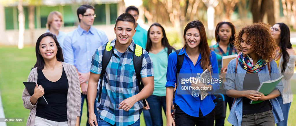 Diverse high school or college students walking on campus : Stock Photo