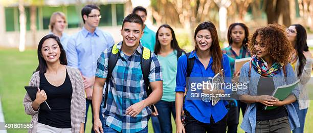 diverse high school or college students walking on campus - middelbare scholier stockfoto's en -beelden