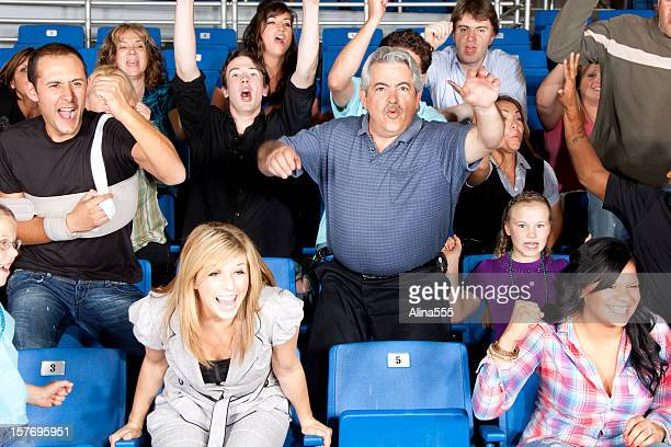 Diverse large group of excited people cheering at a game