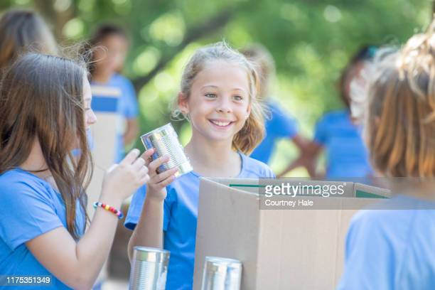 diverse little girls collect canned food during community donation drive - selfless stock pictures, royalty-free photos & images