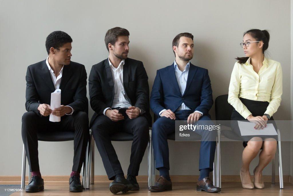 面接を待っている女性のライバルを見て多様なオスの志願者 : ストックフォト