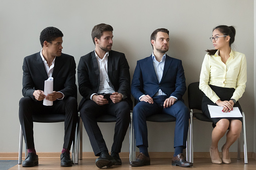 Diverse male applicants looking at female rival waiting for interview 1129629362
