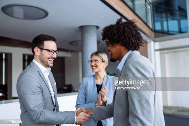 diverse male employees shaking hands in hallway - gratitude stock pictures, royalty-free photos & images